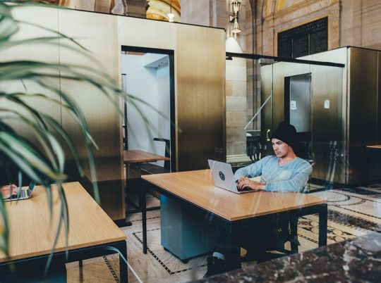 A man in a beanie working on a laptop at a desk in an open office space